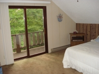 Bedroom on upper level features sliding glass doors to deck with view of golf course.